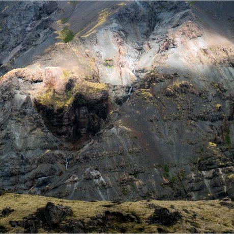 Die steilen Hänge der Hellisskógsheiði werden von der Sonne beschienen